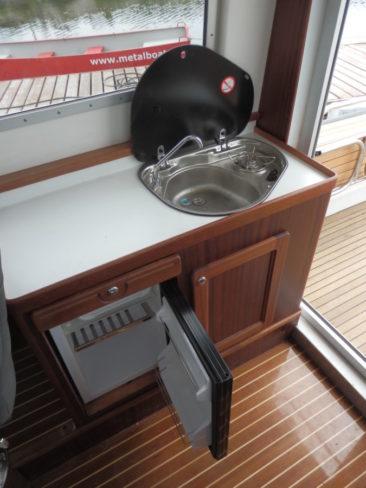 Справа размещен камбузный блок с холодильником и мойкой, объединенной с газовой плитой
